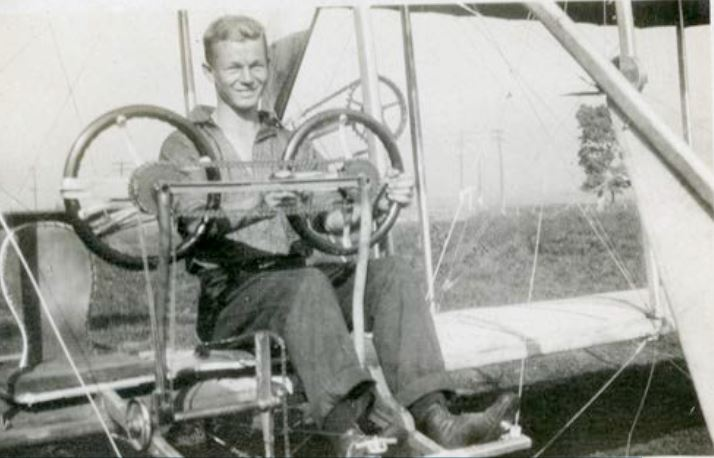 Roy sitting at the controls of a Wright School airplane
